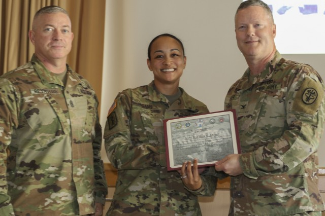 Command Sgt. Maj. Thurman Reynolds (left), command sergeant major, Landstuhl Regional Medical Center, and Col. Michael Weber (right), commander, LRMC, present Sgt. Maj. Tres Bien B. Adams, sergeant major, Dental Health Command Europe, with a certificate of appreciation for her contributions during LRMC's 2019 Women's Equality Day Observance, Aug. 26. The observance celebrated strives the U.S. military has made toward gender equality while recognizing continuing struggles for women around the world.