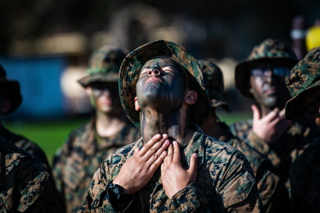 A Marine assigned to 'Academic' Company applies face paint during battle skills training at the Presidio of Monterey, California, Aug. 30, 2019.