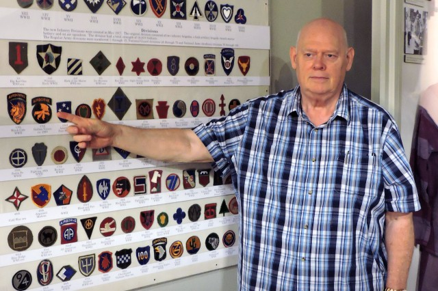 Field Artillery Museum volunteer Steven Burns drew on his contacts with collectors who swap shoulder patches to round up a complete collection of them for the museum's new gallery. Here he points out one of the more popular ones, The Golden Talon of the 17th Airborne Corps.