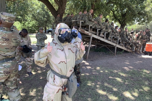 A Congressional staff member gives a thumbs up after donning a MOP suit during an indoctrination to Basic Combat Training at Fort Sill, Okla.