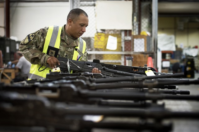 Staff Sgt. Samuel Oteroreyes, weapons quality assurance, 401st Army Field Support Battalion-Kuwait, selects another M240C machine gun for final verification in the weapons maintenance facility of Army Prepositioned Stocks-5, Aug. 26, Camp Arifjan, Kuwait.