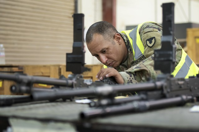 Staff Sgt. Samuel Oteroreyes, weapons quality assurance, 401st Army Field Support Battalion-Kuwait, inspects a line of M240C machine guns in the weapons maintenance facility of Army Prepositioned Stocks-5, Aug. 26, Camp Arifjan, Kuwait.