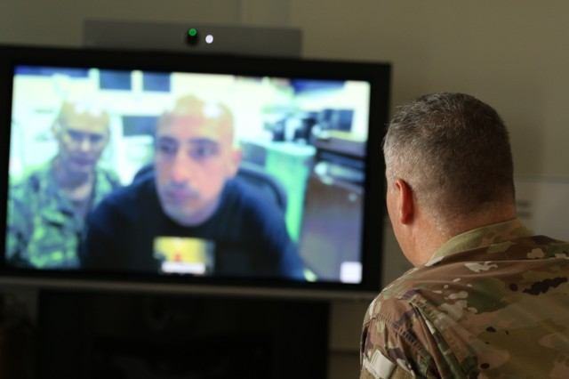 U.S. Army Col. Michael Weber, commander, Landstuhl Regional Medical Center, interacts with U.S. Navy Cmdr. Jason Johnson (background on monitor), director of surgical services, Expeditionary Medical Facility Djibouti, Camp Lemonnier, Djibouti, and the first patient connected from EMF Djibouti to LRMC via virtual health technology recently implemented at the U.S. Navy's EMF, Aug. 28. The secured connection allows over 300 physicians in over 40 medical specialties at LRMC the ability to make face-to-face medical consultations with patients at EMF Djibouti, enhancing the EMF's capability and virtually deploying LRMC physicians to Service Members throughout Africa. LRMC is the largest American medical center outside the United States and the only American College of Surgeons verified Level III Trauma Center overseas.