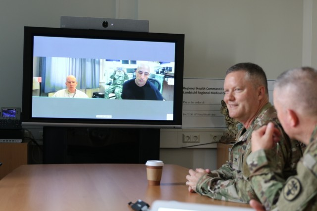 U.S. Army Col. Michael Weber (right), commander, Landstuhl Regional Medical Center, interacts with Dr. Mark Marilley (left side of monitor), the first physician to utilize the virtual health technology with the U.S. Navy's Expeditionary Medical Facility Djibouti, Camp Lemonnier, Djibouti, via virtual health technology recently implemented at the U.S. Navy's EMF, Aug. 28. The secured connection allows over 300 physicians in over 40 medical specialties at LRMC the ability to make face-to-face medical consultations with patients at EMF Djibouti, enhancing the EMF's capability and virtually deploying LRMC physicians to Service Members throughout Africa. LRMC is the largest American medical center outside the United States and the only American College of Surgeons verified Level III Trauma Center overseas.