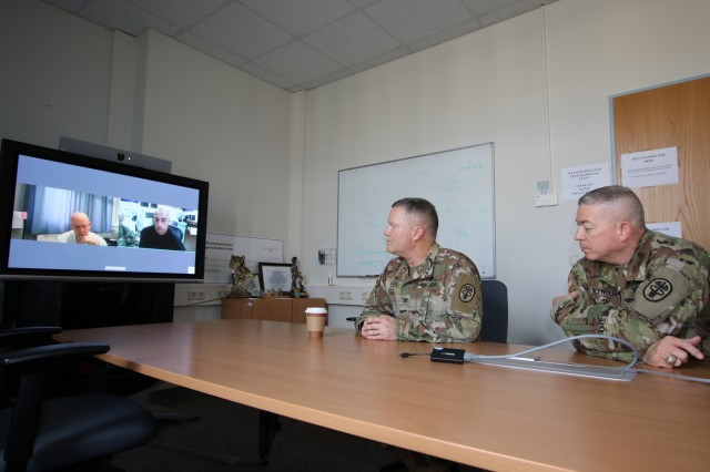 U.S. Army Col. Michael Weber, commander, Landstuhl Regional Medical Center, and Command Sgt. Maj. Thurman Reynolds, command sergeant major, LRMC, interact with Dr. Mark Marilley (left side of monitor), the first physician to utilize virtual health technology from LRMC with the first patient (right side of monitor) at the U.S. Navy's Expeditionary Medical Facility Djibouti, Camp Lemonnier, Djibouti, via virtual health technology recently implemented at the U.S. Navy's EMF, Aug. 28. The secured connection allows over 300 physicians in over 40 medical specialties at LRMC the ability to make face-to-face medical consultations with patients at EMF Djibouti, enhancing the EMF's capability and virtually deploying LRMC physicians to Service Members throughout Africa. LRMC is the largest American medical center outside the United States and the only American College of Surgeons verified Level III Trauma Center overseas.
