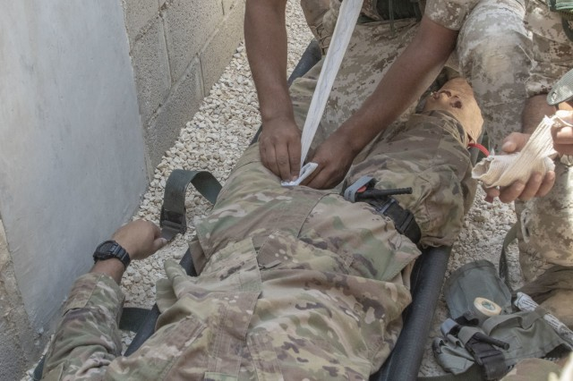 A Jordan soldier, with 7th Mechanized Battalion, 48th Mechanized Brigade, treats a notional leg wound on a U.S. Army Soldier, with 1st Squadron, 102nd Cavalry Regiment, 44th Infantry Brigade Combat Team of the 42nd Infantry Division, New Jersey National Guard, during medical evacuation training, part of the Jordan Operational Engagement Program at Joint Training Center-Jordan August 27, 2019. The Army is optimizing for interoperability with all our allies and partners to strengthen alliances and deliver more effective coalition operations.
