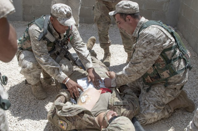 Jordan soldiers, with 7th Mechanized Battalion, 48th Mechanized Brigade, medically treat a notional abdominal wound on a U.S. Army Soldier, with 1st Squadron, 102nd Cavalry Regiment, 44th Infantry Brigade Combat Team of the 42nd Infantry Division, New Jersey National Guard, during medical evacuation training, part of the Jordan Operational Engagement Program at Joint Training Center-Jordan August 27, 2019. The Army is optimizing for interoperability with all our allies and partners to strengthen alliances and deliver more effective coalition operations.