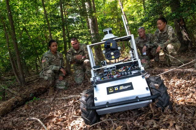 Army researchers simulate a patrol where a ground robot, acting as a forward observer, has detected a possible enemy position. It has relayed this information to the rest of the squad, who then plan their next move.