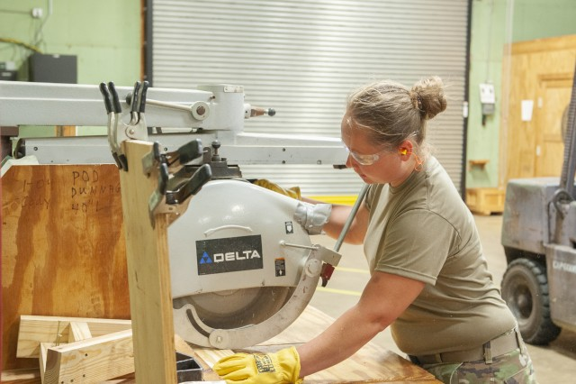 Spc. Kari Calkins cuts a board to build a new block in the Anniston Munitions Center's carpentry shop. ANMC uses the blocks to secure munitions during shipment. Calkins is part of the 395th Ordnance Company from Wisconsin, which trained at the Anniston Munitions Center July 13 to Aug. 23.
