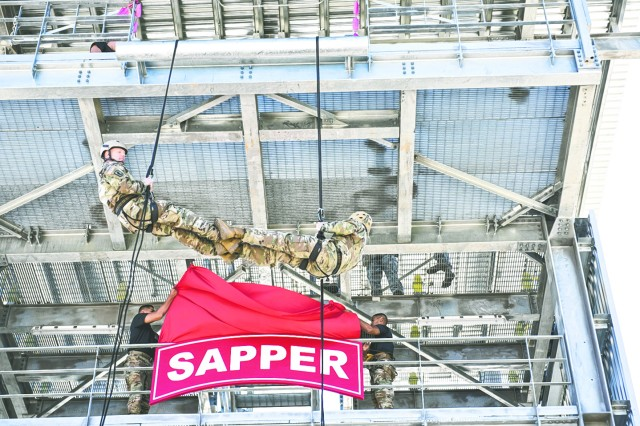 1st Engineer Brigade Commander Col. Kip Korth and Command Sgt. Maj. Robert Ferguson rappel down the new Sapper Leader Course tower and pause as a new Sapper tab sign is unveiled.