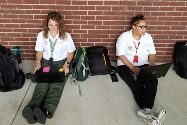 Lauren Beasley, Action officer (left) and Alex Duckett, Mission Specialist (right), working at the South Carolina State Emergency Operations Center in Columbia making use of the front porch as they wait for an all-hands meeting to begin. Power Team members show great flexibility and patience as they prepare to help those affected by Hurricane Dorian.