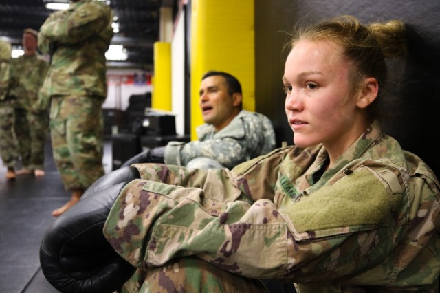 Spc. Audrey J. Holland, a combatives instructor for the United States Army Combatives School at Fort Bragg, N.C., stares as fighters go head-to-head in the culminating event of her class July 10, 2019. She is the youngest instructor at the school and has only been training there for the last seven months.