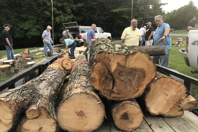 Members of the Tuckessee Woodturners club unload logs harvested from the Task Force 3-502nd Memorial Park. The logs will be carved into wooden bowls and given as keepsakes to surviving Family members of the Gander crash.