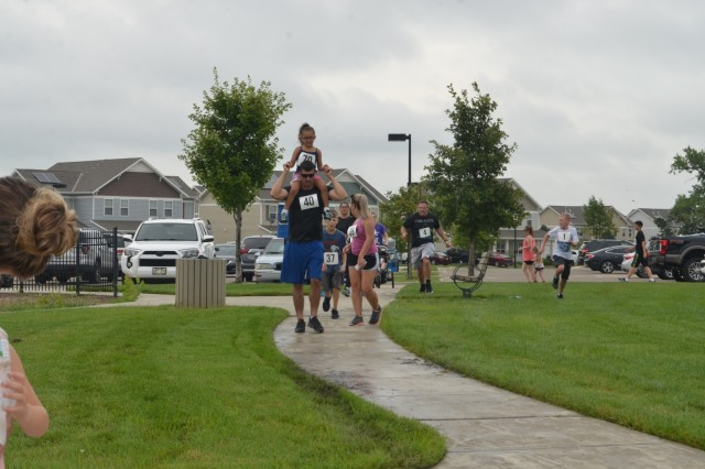Fort Riley residents raced and rode, their way through the Colyer Forsyth neighborhood Aug. 10 during the Corvias Back-to-School fun run. Free backpacks for the children were given away as they prepared for the first day of school.