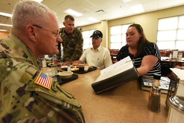 Maj. Gen. John Evans Jr. (left), commanding general of U.S. Army Cadet Command and Fort Knox, and Garrison Commander Col. CJ King (standing) look at an album full of memories collected by Howell Moore (seated center) during a veteran visit of Fort Knox Sept. 6, 2019. Moore is a World War II combat veteran, one of two that participated in the visit.
