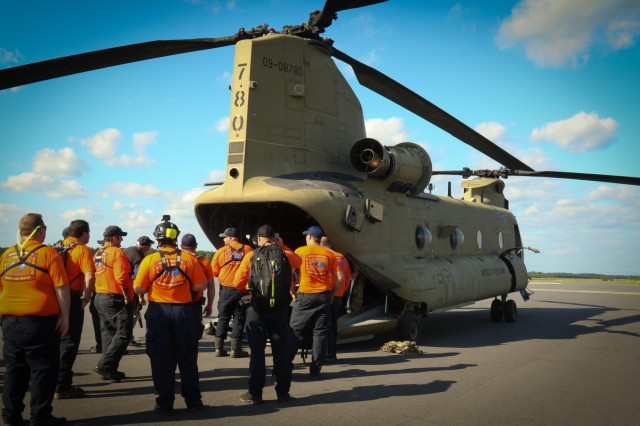 North Carolina and South Carolina National Guardsmen and members of the North Carolina Search and Rescue Task Force 2 prepare for departure in a CH-47 Chinook at an airport in Kinston County, Sept. 6, 2019. NG service members, N.C. Emergency Management and state partner agencies work as a cohesive unit to prepare for, respond to and recover from the effects of Hurricane Dorian. (U.S. Army National Guard photos by Spc. Hannah Tarkelly, 382nd Public Affairs Detachment/Released)