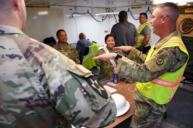 : U.S. Army Lt. Col. Gordon Vincent meets with members from U.S. Transportation Command and the 25 Infantry Division's 3rd Armored Brigade Combat Team during port operations at the Port of Port Arthur, Texas, September 6, 2019.