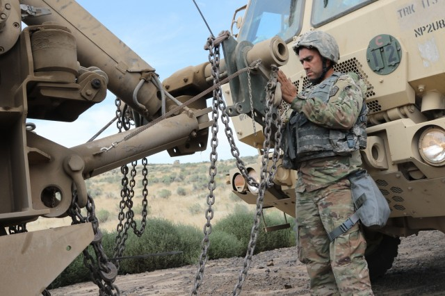 Cpl. Jonathon Sexton from the 1844th Transportation Company, 108th Sustainment Brigade works on attaching the recovery vehicle's towbar to the downed truck. Rising Thunder 2019 is an annual exercise joining the U.S. Army and the Japanese Ground Self-Defense Force (JGSDF) and is part of Pacific Pathways 19-3. Rising Thunder 2019 is also a United States Army Pacific-sponsored capstone event featuring U.S. Army units from the 7th Infantry Division and the Illinois Army National Guard's 33rd Infantry Brigade Combat Team and 108th Sustainment Brigade. (Illinois Army National Guard photo by Spc. Shaylin Quaid)