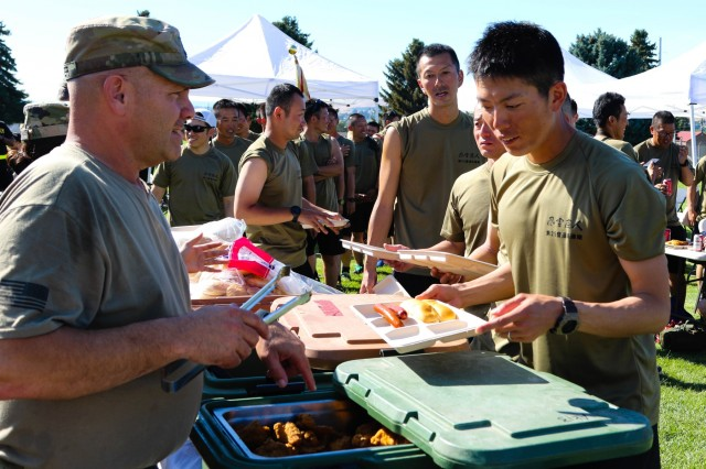 YAKIMA, Wash. - Soldiers from the Illinois Army National Guard serve food to soldiers from the Japan Ground Self-Defense Force on sports day at Rising Thunder 19 at Yakima Training Center, Washington, Sep. 4, 2019 . Rising Thunder 2019 is an annual exercise between the U.S. Army and the Japan Ground Self-Defense Force featuring units from the 7th Infantry Division, the Illinois Army National Guard's 33rd Infantry Brigade Combat Team and 108th Sustainment Brigade, and Japan's 25th Infantry Regiment. The exercise, held Aug. 28 - Sept. 13 at Yakima Training Center in Yakima, Washington, consists of company/platoon unilateral and bilateral training events in two phases, culminating with a bilateral live fire exercise. (U.S. Army Reserve photo by Sgt. James Barrington)