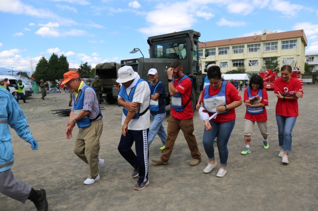 Volunteers from the Camp Zama American Red Cross, role-playing as injured victims, are escorted to a medical checkpoint during the annual Zama City disaster drill, held Sept. 7 at Zama Elementary School near Camp Zama, Japan.