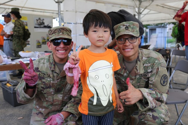 Staff Sgt. Karim Acosta, left, and Sgt. 1st Class Tatiana Mason, left, assigned to U.S. Army Medical Department Activity--Japan, pause for a photo with a young volunteer role-player after putting special-effects makeup on his arm during the annual Zama City disaster drill, held Sept. 7 at Zama Elementary School near Camp Zama, Japan.
