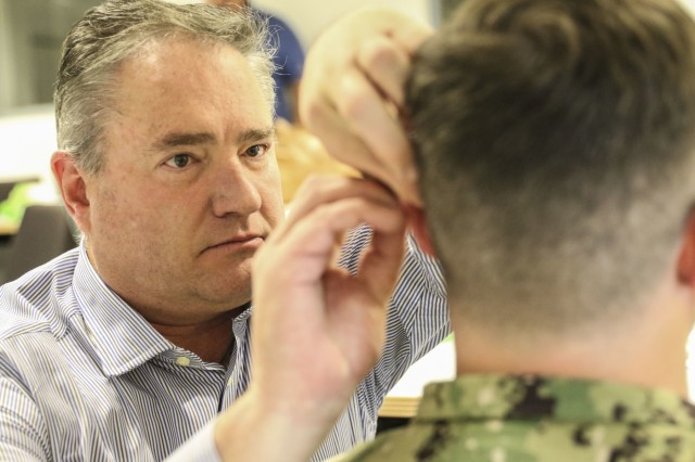 Aaron Castle, a primary care physician at Wiesbaden Army Health Clinic, practices acupuncture as a form of pain management during Landstuhl Regional Medical Center's Traumatic Brain Injury and Rehabilitation Clinic's TBI Champion Training Conference, at Ramstein Air Base, Germany, Sept. 6. The three-day conference assembled medical professionals across Europe and Western Asia to promote standardization of TBI clinical care by sharing knowledge, current recommendations and best practices.