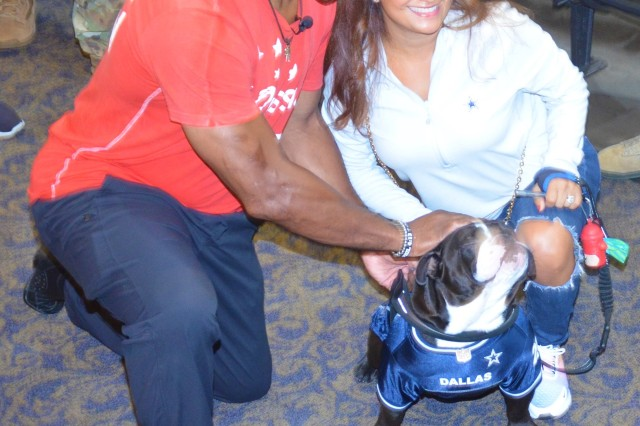 Herschel Walker, left, poses with Maria Smith, the wife of retired Command Chief Master Sgt. Kenellias Smith, the former 446th Airlift Wing command chief master sergeant, and Tux, an Instagram bulldog model, at Carey Theater on Joint Base Lewis-McChord Sept. 10. Walker won the 1982 Heisman Trophy while playing for the University Of Georgia Bulldogs.