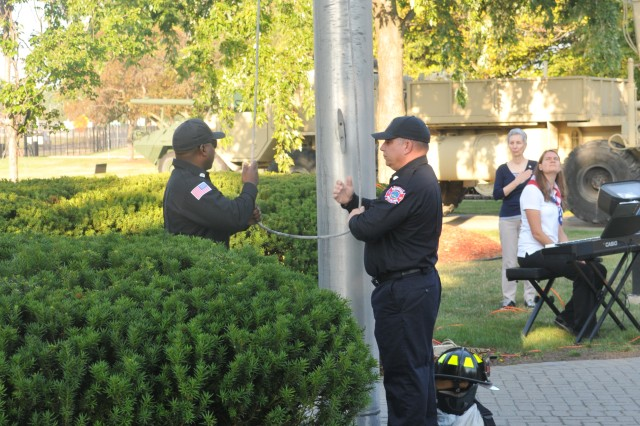 An honor guard comprised of Detroit Arsenal firefighters lowers the installation flag in honor of those killed September 11, 2001 during the Patriot Day Observance.