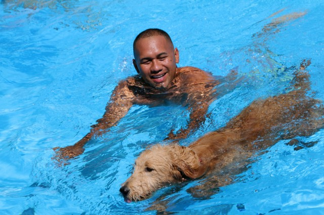 Brenton Kaonohi swims with his golden doodle dog Kameli Sept. 7, 2019, at Quinette Pool. About 40 dogs and their owners participated in Fort Sill first Dog Days of Summer pool party.