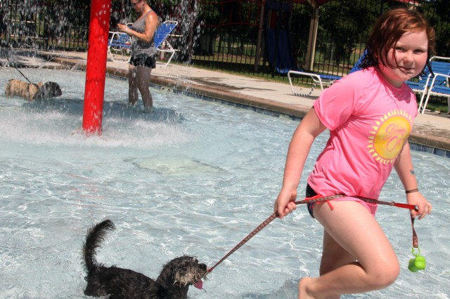 Bethany Little, 9, and her dog Susie romp around at the spray park at Quinette Pool. The Dog Days of Summer party was free and open to the public.