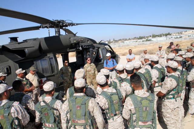 U.S. Army Sgt. Michelle Shinafelt, center, flight medic, Golf Company, 5th Battalion, 159th Aviation Regiment, talks to members of Jordan Armed Forces' 7th Mechanized Infantry Battalion about proper loading procedures during medical evacuation training prior to exercise Eager Lion 2019 beginning on Aug. 21, 2019. This multinational exercise is U.S. Central Command's premiere exercise in the Levant region and is a major training event that provides U.S. forces, Jordan Armed Forces and 28 other participating nations the opportunity to improve their collective ability to plan and operate in a coalition-type environment. (U.S. Army Reserve photo by Sgt. Zach Mott)