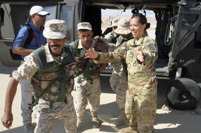 Soldiers with the Jordan Armed Forces' 7th Mechanized Infantry Battalion move away from a medical evacuation helicopter after loading a simulated casualty as U.S. Army Sgt. Michelle Shinafelt, right, flight medic, Golf Company, 5th Battalion, 159th Aviation Regiment, directs them during medical evacuation training in preparation for exercise Eager Lion 2019, Aug. 21, 2019. This multinational exercise is U.S. Central Command's premiere exercise in the Levant region and is a major training event that provides U.S. forces, Jordan Armed Forces and 28 other participating nations the opportunity to improve their collective ability to plan and operate in a coalition-type environment. (U.S. Army Reserve photo by Sgt. Zach Mott)