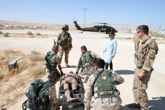 Soldiers from the Jordan Armed Forces' 7th Mechanized Infantry Battalion prepare to move a simulated casualty while U.S. Army Sgt. Michelle Shinafelt, standing left, flight medic, Golf Company, 5th Battalion, 159th Aviation Regiment, observes as part of medical evacuation training in preparation for exercise Eager Lion 2019, Aug. 21, 2019. This multinational exercise is U.S. Central Command's premiere exercise in the Levant region and is a major training event that provides U.S. forces, Jordan Armed Forces and 28 other participating nations the opportunity to improve their collective ability to plan and operate in a coalition-type environment. (U.S. Army Reserve photo by Sgt. Zach Mott)