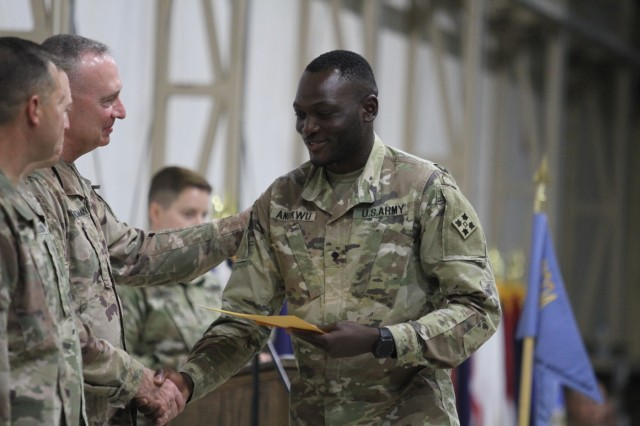 Army Spc. Augustine Anukwu, right, distinguished leadership awardee, 1st Battalion, 8th Infantry Regiment, 3rd Armored Brigade Combat Team, 4th Infantry Division, Task Force Spartan, shakes hands with Command Sgt. Maj. Dan Churchman, commandant, Camp Buehring Noncommissioned Officer Academy, after being presented with his graduation certificate. Anukwu separated himself from his peers through his leadership abilities throughout the course.