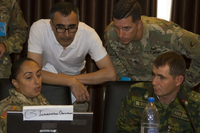 From left, Army Staff Sgt. Myrna Bistros, intelligence support to information operations for exercise Regional Cooperation 2019, 303rd Information Operations Battalion, 151st Theater Informations Operations Group, United States Civil Affairs and Psychological Operations Command; Daler Djavadov, Tajikistan linguist for RC19; Army Sgt. 1st Class Jeremy Brown, operations sergeant major for RC19, 51st Troop Command, Massachusetts Army National Guard; and Tajik Army Capt. Nope Muhammad, information operations, Task Force Patriot; all discuss exercise operations during Regional Cooperation 2019 at Dushanbe, Tajikistan, August 10, 2019. Exercise Regional Cooperation is an annual exercise to help strengthen military-to-military relationships between the United States and partners in Central and South Asia. The exercise enhances regional security and stability among the participating nations. (U.S. Army Reserve photo by Spc. Ashton Koller)