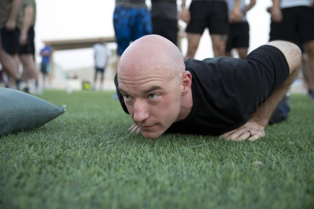 Major Michael Wilson, communications integration and engineering branch chief, Combined Joint Task Force - Operation Inherent Resolve, XVIII Airborne Corps, prepares to do the pushup event during a special physical training competition celebrating the 75th anniversary of the XVIII Airborne Corps on Camp Arifjan, Kuwait, August 22, 2019. The XVIII Airborne Corps was born August 25, 1944 in Osbourne, St. George, England from the XVIII Corps during World War II, assuming command of the 82nd Airborne and 101st Airborne Divisions, as part of the preparation for Operation Market Garden. (U.S. Army Reserve photo by Sgt. Jennifer Shick)