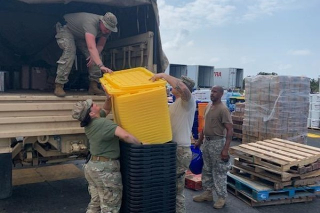Combat Medic and North Carolina National Guardsman, Sgt. Wesley Brantley (standing in the truck) and some of his team members Spc. Ruben Baca (right) and Spc. Kaileigh Deanda (left), of the 105th Engineering Battalion, Headquarters and Headquarters Company, based in Raeford, North Carolina, load their MTV (high-water vehicle) with tactical bins to help in the preparation of rescue operations in Clinton, North Carolina, on September 5, 2019. Hurricane Dorian's weather consist of tornadoes, heavy rain and coastal damage resulted to 38 historic sites suffering major damage like Portsmouth.
