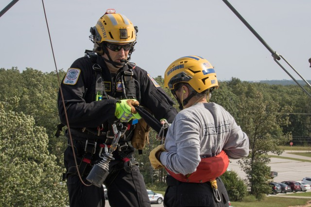 Josh Boehm, Missouri Task Force 1 Helicopter Search and Rescue technician, prepares Mary Roy, a K9 Search and Rescue specialist, for extraction during rescue training Sept. 10 on Fort Leonard Wood.