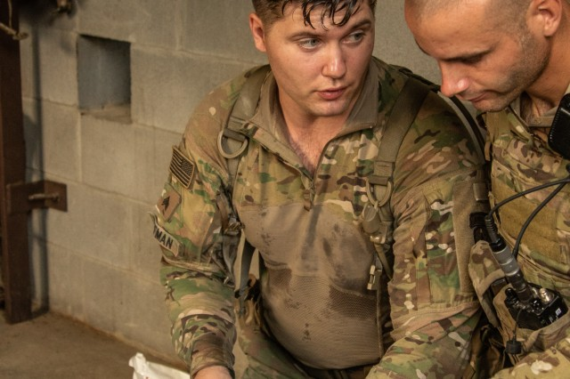 Sgt. Christopher Huffman, a combat medic specialist advisor assigned to 1st Security Force Assistance Brigade, treats a simulated casualty for a possible spinal injury during the Advisor Forge training exercise at Fort Benning, GA, August 14, 2019. A requirement of the evaluation is to maintain manual stabilization of the head and neck area until analysis is complete. (U.S. Army photo by Pfc. Daniel J. Alkana / 22nd Mobile Public Affairs Detachment)