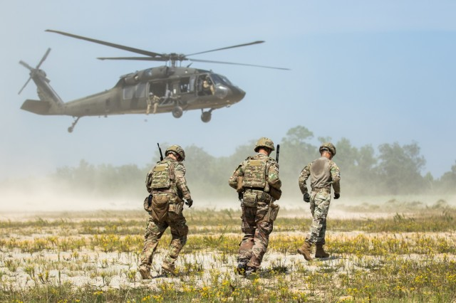 Advisors from 1st Security Force Assistance Brigade, approach a A UH-60L Black Hawk for sling load transportation during the Advisor Forge training exercise at Fort Benning, GA,  August 13, 2019. The group of advisors were tasked with connecting the load to the helicopter undercarriage. (U.S. Army photo by Pfc. Daniel J. Alkana/ 22 Mobile Public Affairs)