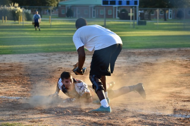 "Sgt. Jamal Walker, 3rd baseman for the 3rd Infantry Division, Division Headquarters and Headquarters Battalion team, the ""Legion"", attempts to tag out Sgt. Michael Thompson, left fielder for the 1st Battalion, 41st Field Artillery Regiment, 1st Armored Brigade Combat Team, team the ""Charlie Dogs,"" during the intramural softball championship game at Fort Stewart, Ga., Aug. 29. Thompson was called safe, and eventually scored a run. Legion took the win and the championship trophy, 17-8. (U.S. Army Photo by Spc. Jordyn Worshek, Released)"