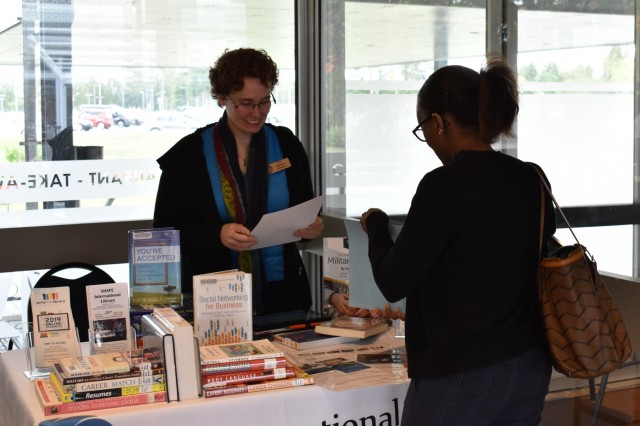Lara  Harrison,  SHAPE  International  Library  employee,   talks   to   an   event   attendee   during   the   Benelux    Employment,  Career  and  Volunteer  Expo  on  Sept.  5, 2019,  at  SHAPE,  Belgium.  The  SHAPE  International Library  employees  were  on-site  to  talk  about  career   resources such as books and online materials available  at  the  library  as  well  as  speak  to  attendees  about volunteer  opportunities.
