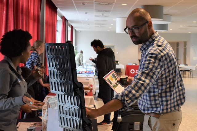 An attendee looks at Child and Youth Services flyers during the Benelux Employment and Career Expo Sept. 5, 2019, on SHAPE, Belgium. CYS was one of the main employers at the event.
