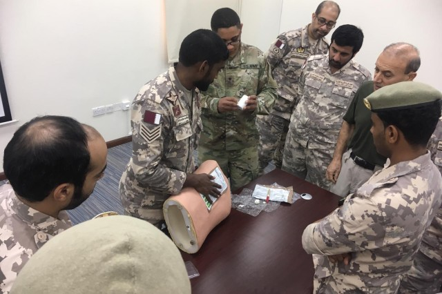 A New Jersey Army National Guard Soldier discusses a Tactical Combat Casualty Care (TCCC) scenario with members of the Qatari Emiri Land Forces (QELF) during a subject matter expert exchange held Sept. 8 -12, 2019, at the Qatar Emiri Land Force Artillery School in Al Rayyan Municipality, Qatar. The weeklong event, a part of the National Guard Bureau's State Partnership Program, provided an opportunity to share knowledge and best practices on TCCC with the QELF to better enhance their performance and understanding of basic lifesaving techniques.