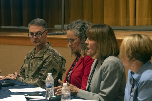 Col. John 'Wes' Hankins, Fort Jackson Garrsion Commander, listens as Paula Cook with Balfour Beatty answers questions during a quarterly town hall held Sept. 10 at the Joe E. Mann ballroom.