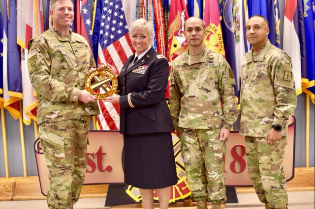CW5 Pennie Temmerman receives the Ordnance Crest from Col. Joseph Colacicco, Assistant Commandant of the Ordnance Corps.  They are joined by CW5 Danny Taylor, Regimental chief warrant officer, and CSM Terry Burton, Regimental Command Sergeant Major, at the U.S. Army Ordnance Crucible's Ammunition Transfer Holding Point (ATHP) Team of the Year event at Fort Pickett, Virginia.  Temmerman, who gave the opening remarks at the event, is the Military Deputy of the Munitions and Logistics Readiness Center at the Joint Munitions Command.