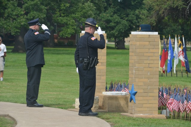 Benjamin Kay, police officer (left) and Capt. Jeff Moritz, firefighter, salute after placing their headgear on top of each pillar of the 9/11 Memorial during a remembrance ceremony held at Rock Island Arsenal Sept. 11. (Photo by Galen Putnam, ASC Public Affairs)