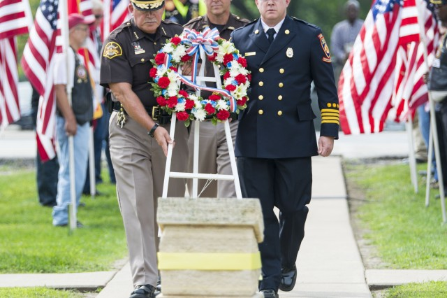 Sheriff Gerry Bustos, Rock Island County Sheriff's Office, Chief Deputy Steve VenHuizen, Rock Island County Sheriff's Office, and Deputy Chief Steve Regenwether, Moline Fire Department, carry the remembrance wreath at the 9/11 Memorial during a ceremony held at Rock Island Arsenal, Illinois, Sept. 11. (Photo by Linda Lambiotte, ASC Public Affairs)