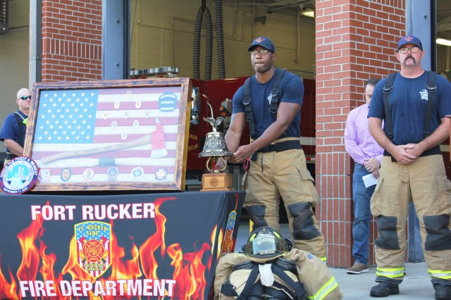 Adonis Eckols, firefighter, rings a bell at the Fort Rucker 9/11 Stephen Siller Moving Tribute as Chris Quattlebaum, firefighter and speaker at the event, looks on Sept. 11 at the Fort Rucker Fire Department.