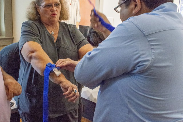 "Sherrilee Demmer, educator for Trauma Services at Brooke Army Medical Center's Trauma Clinic, shows City of San Antonio council staff members how to apply a tourniquet during Stop the Bleed held at the Plaza de Armas building in Downtown San Antonio Aug. 29, 2019. The training consisted of a presentation where attendees learned the ""ABCs of Bleeding Control"" along with some hands-on practice in applying tourniquets, packing wounds and applying direct pressure to stop bleeding."